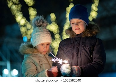 Two cute young children, boy and girl in warm winter clothing holding burning sparkler fireworks on dark night outdoors bokeh background. New Year and Christmas celebration concept.