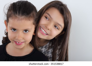 Two cute young girls portrait on bright background