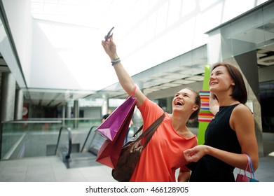 Two cute young lady doing selfie at the Mall. In the hands of girlfriends bright packages with purchases. They are posing and laughing.