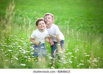 Two cute young preschool siblings playing in green field or meadow.