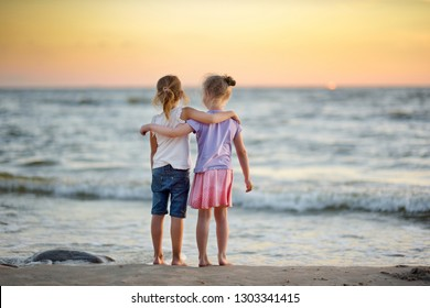 Two cute young sisters having fun on a sandy beach on warm and sunny summer day by the sea. Kids playing by the ocean. Summer activities for children.