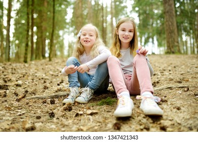 Two cute young sisters having fun during forest hike on beautiful early spring day. Active family leisure with kids. Family fun.