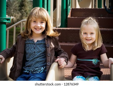 Two cute young sisters holding hands and sitting next to each other in an outdoor playground