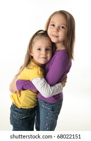 Two cute young sisters standing up hugging each other, isolated on white