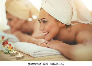 Two cute young women are enjoying during a skin care treatment at a spa.