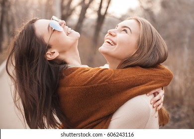 Two cute young women are s hugging and laughing outdoors