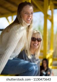 two cute young women smiling and enjoying life on an autumn walk along the ocean