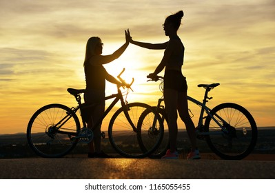 Two cyclist with bicycle in the sunset. Healthy lifestyle concept.