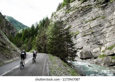 Two cyclists ascend an Alpine road between a gorge as a glacial river plunges alongside them.
