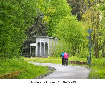 Two cyclists cycle comfortably over the Nordbahn route, which was once a  railway route, in Wuppertal / Germany in April 2018 and enjoy the warm spring days and the blossoming nature.