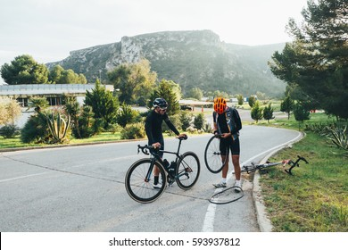 Two cyclists fixing a flat tire on the side of the road in the soft light