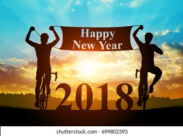 Two cyclists on bicycle at sunset. Forward to the New Year 2018.