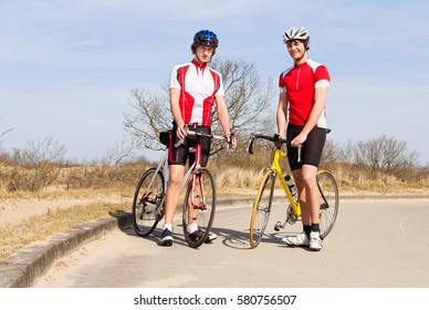 Two cyclists posing with their bicycles
