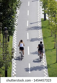 Two cyclists ride bikes on bicycle path
