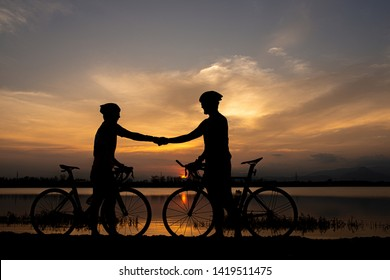Two cyclists shaking hand after finish ride bicycle together. sportsmanship concept.
