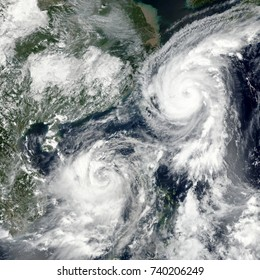 Two Cyclones Stir Up Asian Waters. Typhoons Talim and Doksuri. Elements of this image furnished by NASA.