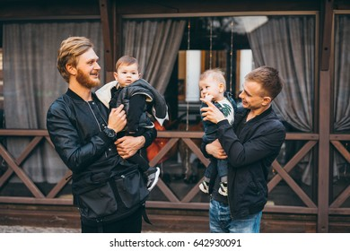 Two dads and their two little boys posing on camera. Spend time outdoors