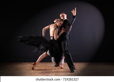 Two dancers in ballroom isolated on black background