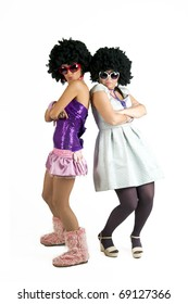 Two dancing girls with sunglasses and afro-styled wigs. Studio shot, isolated on white background