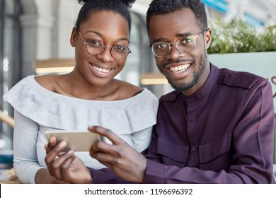 Two dark skinned woman and man with positive smiles, watch video on smart phone, wear glasses, dressed in fashionable clothes, have pleasant expressions. People, ethnicity and technology concept.