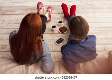 Two dark-haired girl friends sitting on the floor near the sofa at home. Girls listening to music and drinking coffee. View from above.