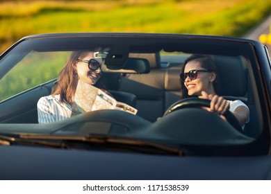 Two dark-haired young women in sunglasses are sitting in a convertible car and smiling on a sunny day. One of them keeps map in her hands.