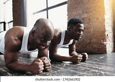 Two dark-skinned athletes stand in a plank position leaning their forearms on floor in the studio. Advertising sports shooting