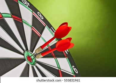 Two Darts in center of the target dartboard on a light green background