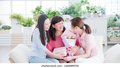 two daughters give flowers to her mom and celebrate happy mother day at home