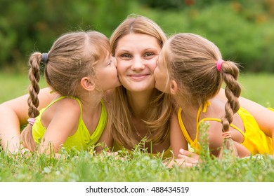 Two daughters kissing mother lying on the grass on a picnic