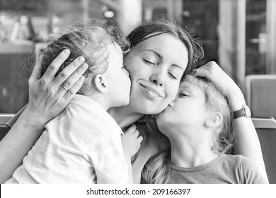 Two daughters kissing their happy mother