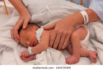 two days new born baby in the caring hands of its mother lying in bed. bar code sign at mother and baby's wrist