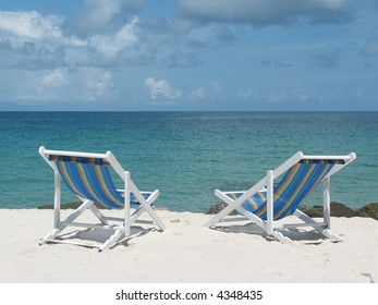 Two deck chairs on pure white sand