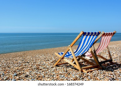 two deckchairs on a pebbled beach, facing out to sea