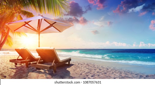 Two Deckchairs Under Parasol In Tropical Beach At Sunset
