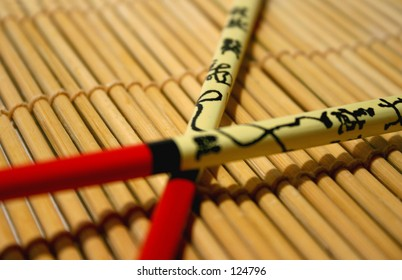 Two decorated chopsticks on a bamboo mat.