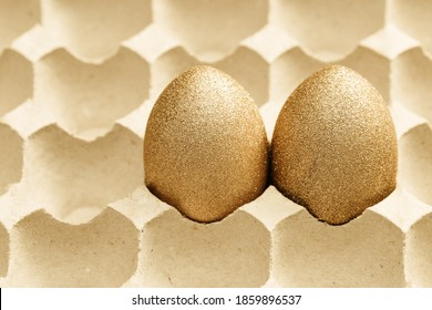Two Decorated Easter golden eggs in cardboard egg tray. Happy Easter background, Creative spring image with painted chicken eggs together.