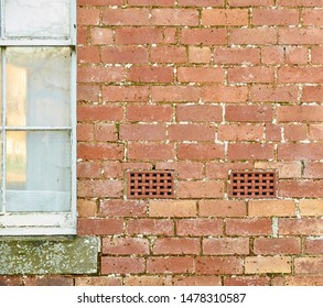 Two decorative Air Vents situated within the walls of a red brick Cottage, next to a wooden single paned Window.