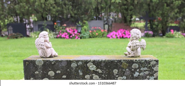 Two decorative angel figures on the top of the gravestone watching towards the other graves on a rainy autumn day. The gravestone is old and covered by lichen. Concepts of death, faith and after life.