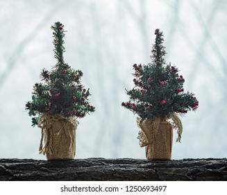 Two decorative artificial Christmas trees, decorated with small red balls, in pots wrapped with coarse canvas, placed on a log, against a  light winter background.