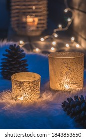 Two decorative glasses with tea lights on a lambskin on a veranda in the blue hour, fairy lights and candle light in the background, cozy atmoshpere, vertical stock photo