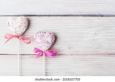 Two decorative Valentines hearts over white wooden background
