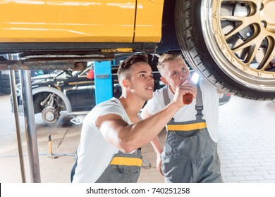 Two dedicated auto mechanics tuning a car through the modification of the rims, while working together in a modern automobile repair shop