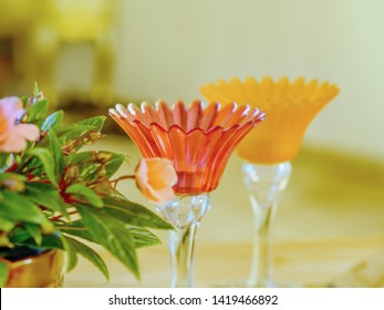 two delicate glass candlesticks in delicate colors with flowers to the side, a still life with a soft, very romantic ambience and soft, calm bokeh, close-up focus in the foreground