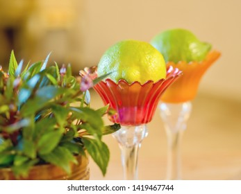 two delicate glass vessels in delicate colors with flowers to the side and inside a fresh citrusfruit   a still life with a soft, very romantic ambience and soft, calm bokeh, close-up focus foreground