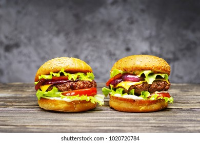 Two delicious beef burgers, with cheese, vegetables and lettuce, hand made, according to a classic recipe on a wooden table.