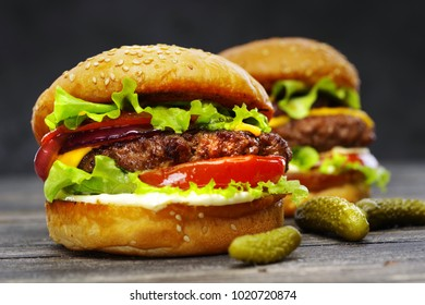 Two delicious beef burgers, with cheese, vegetables and lettuce, hand made, according to a classic recipe on a wooden table. Close-up.