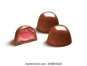 Two delicious chocolate bonbons with half showing starwberry filling, isolated