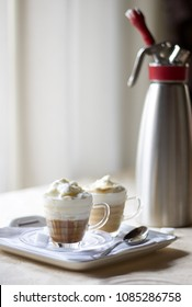 two delicious  cup of coffee cream on the table near a  kitchen siphon