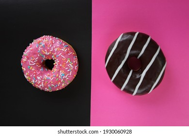 Two delicious donuts on a two-tone background. On a black background, a donut with pink glaze, and on a pink background, a donut with chocolate. Colorful minimalism concept. Free space for text